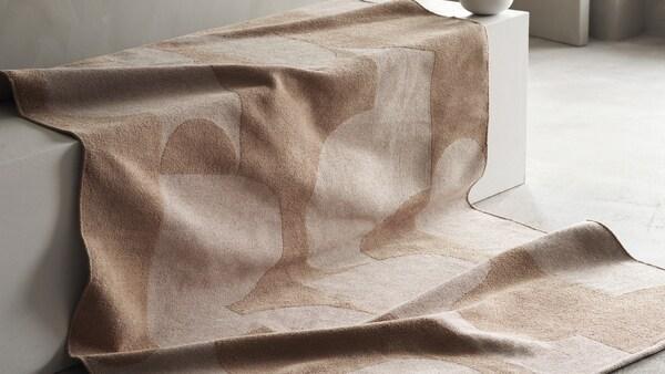 RÖDASK tæppe ligger hen over et trappetrin af beton, der fremhæver tæppets grafiske mønster og jacquard-vævning.