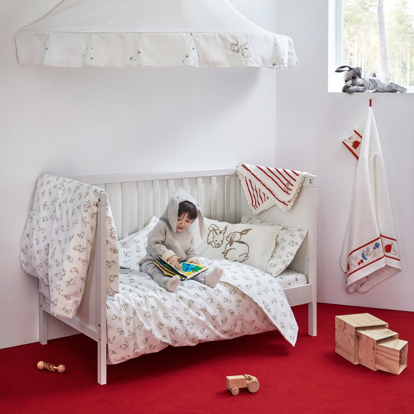 RÖDHAKE baby textile collection with a friendly pattern found on the quilt covers, a blanket, bed canopy and more.