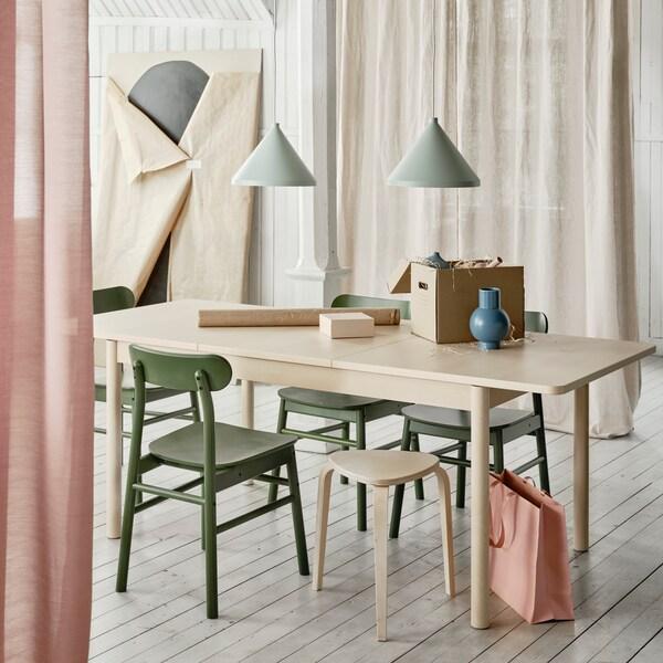 RÖNNINGE bord står i ett ljust rum där färgerna går i pastelltoner med lampa ovanför bordet och en garding på sidan