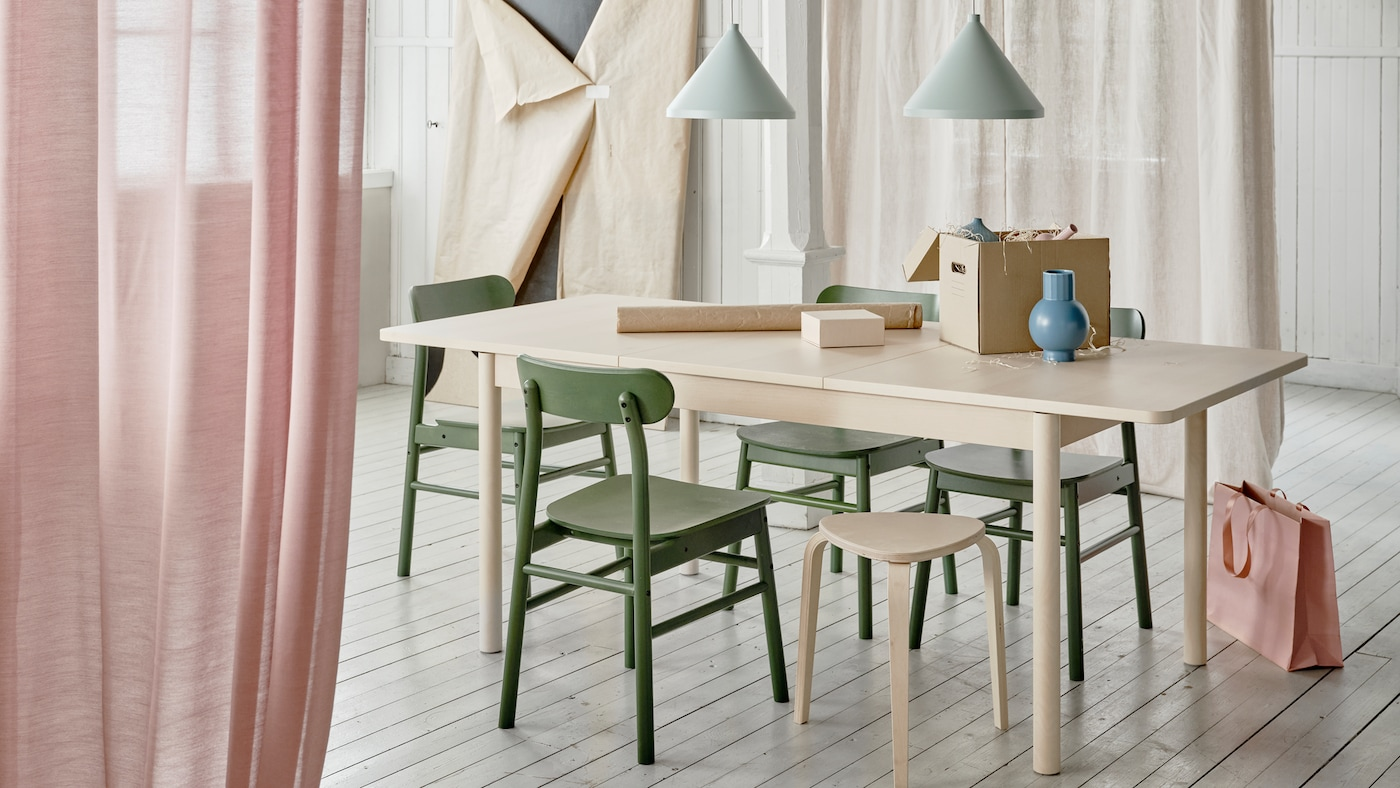 RÖNNINGE extendable table with its extension in use is placed in a dining room context with an ongoing wrapping activity.
