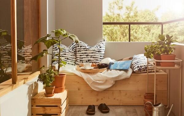 Roh balkóna s dreveným sedením s vankúšmi, posteľou plachtou a podnosom so skromnými raňajkami.