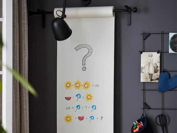 Roh místnosti, role papíru s nakresleným matematickým úkolem.