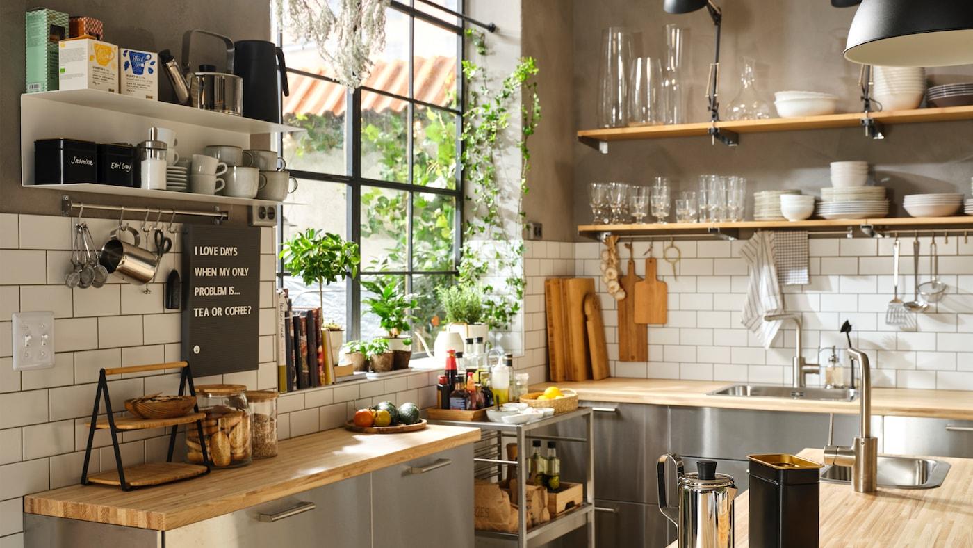 Roh veľkej kuchyne s veľkým oknom, drevenými pracovnými doskami, dvierkami a čelami zásuviek z nehrdzavejúcej ocele a otvorenými policami na riad.