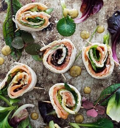 Roliños con salmón mariñado e salsa de mostaza, servidos sobre unha bandexa de mármore decorada con follas de ensalada e herbas recollidas, vistos dende arriba.