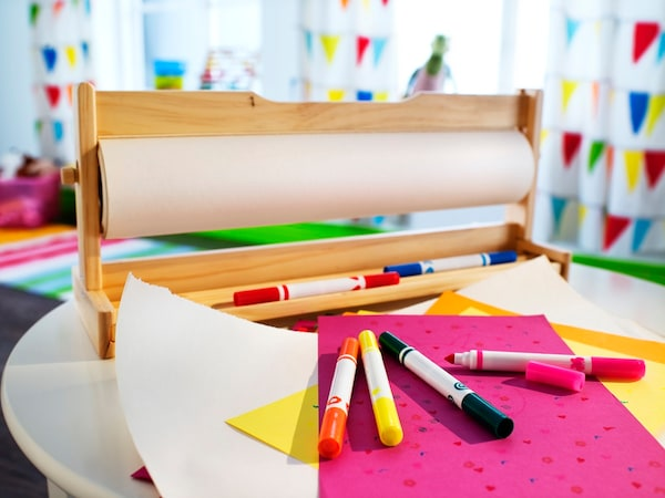 roll of craft paper on a wooden dispenser surrounded by colorful markers and other paper