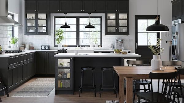 Romslig svart og hvitt kjøkken i klassisk stil med svartbeisede skapdører, hvite benkeplater og kjøkkenøy.
