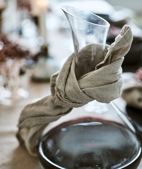 Rond een glazen karaf met rode wijn is een natuurlijk gekleurd linnen servet gebonden om wijndruppels op te vangen.