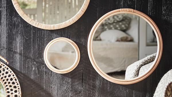 Ronde spiegels in verschillende maten met rotan lijsten hangen aan een donkere, houten oppervlak en vormen het middelpunt van de kamer.