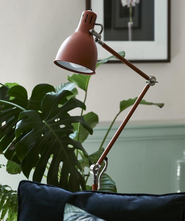 Roodbruine staande lamp in een kamer met planten