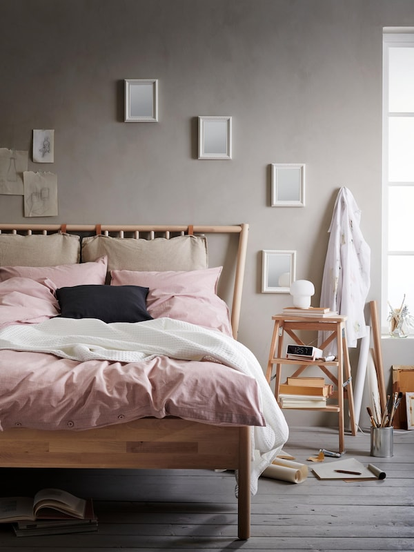 Room with a wooden bed, casually made with pink and white textiles.