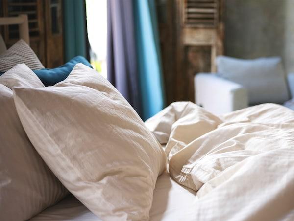 Ropa de cama de satén en beige claro sobre una cama en un dormitorio.