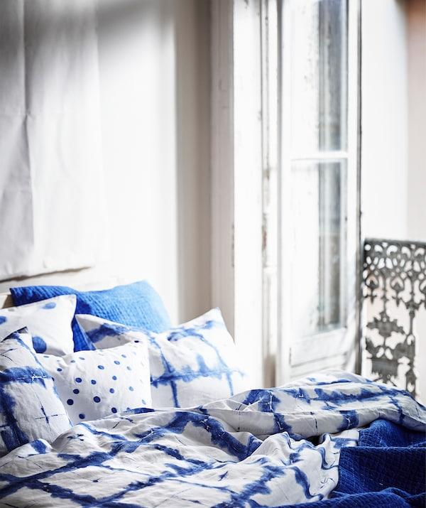 Ropa de cama TÄNKVÄRD con motivos azules colocada en capas sobre una cama al lado de la puerta de un balcón.