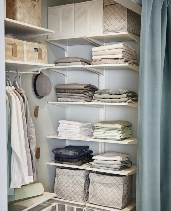 Ropa plegada y cajas en estantes abiertos y ajustables ALGOT dentro de un pequeño vestidor.