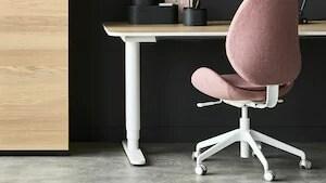 Rosa, stoppad skrivbordsstol i ett mörkt rum.