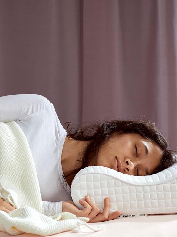 흰 셔츠를 입은 갈색 머리 여성이 ROSENSKÄRM 로센셰름 인체공학적 베개를 베고, 화이트 담요를 덮은 채 자고 있는 모습.
