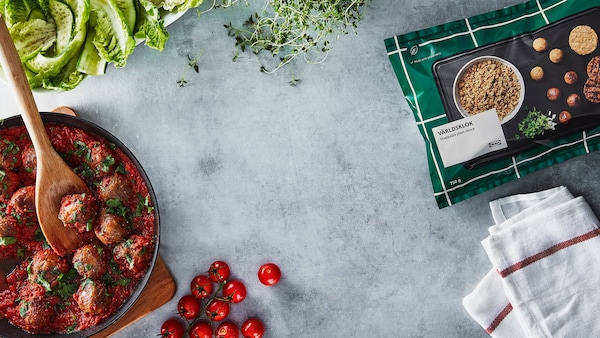Rostlinné kuličky IKEA na černé pánvi s rajčatovou omáčkou.