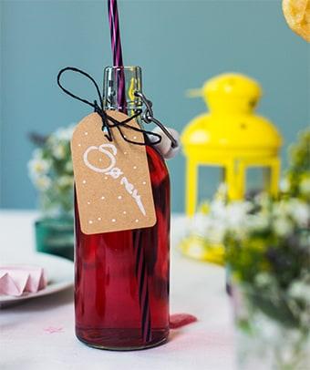 Rot gefüllte Glasflasche, die als Namenskärtchen dient