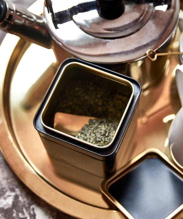 Round, golden tray with tea making kit on it: kettle, a tin with its lid off revealing green tea inside, cups on the side.