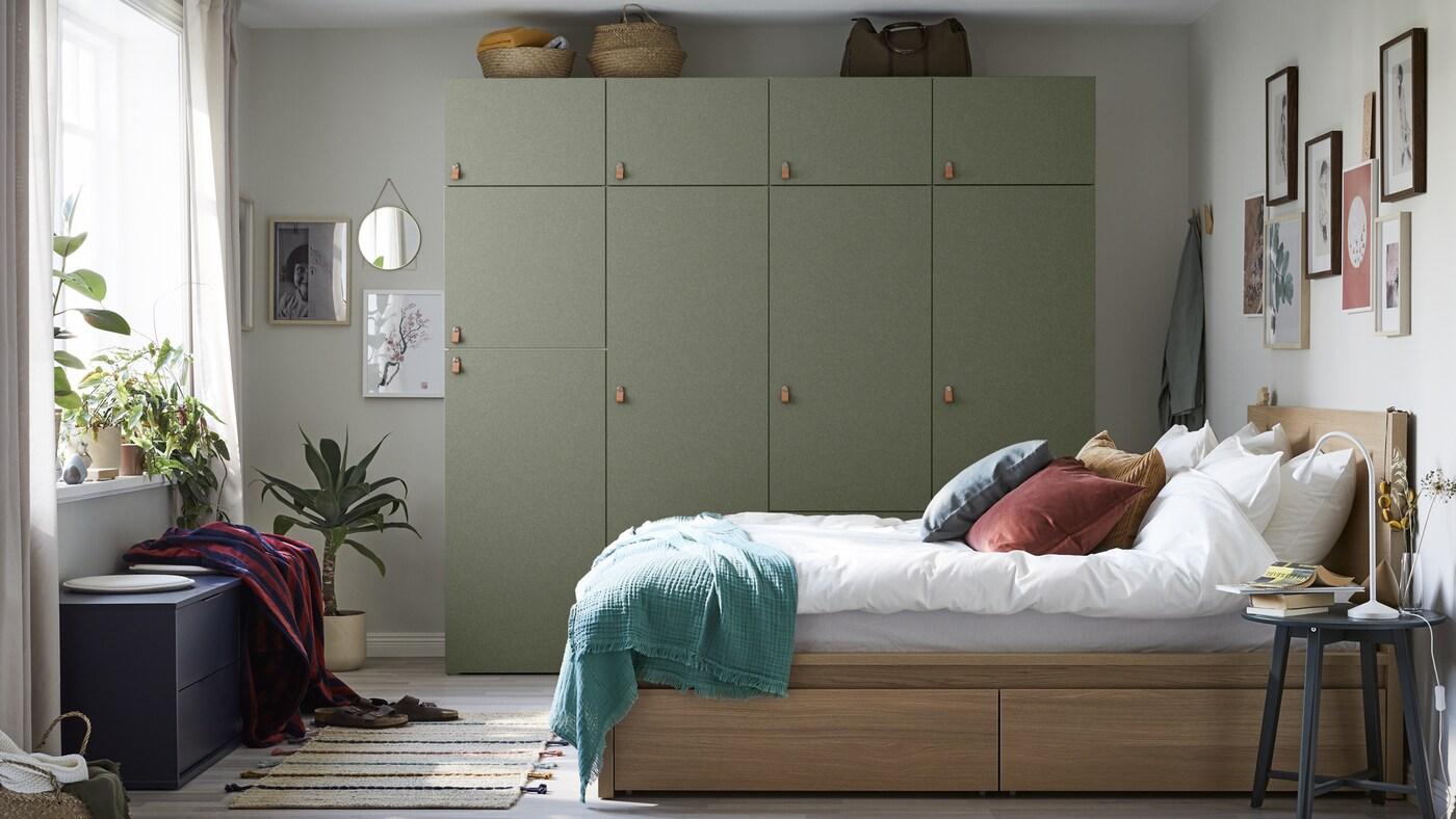 Roupeiro grande em verde encostado a uma parede cinzenta. Cama em madeira com lençóis brancos e almofadas em tons de vermelho, azul e castanho.