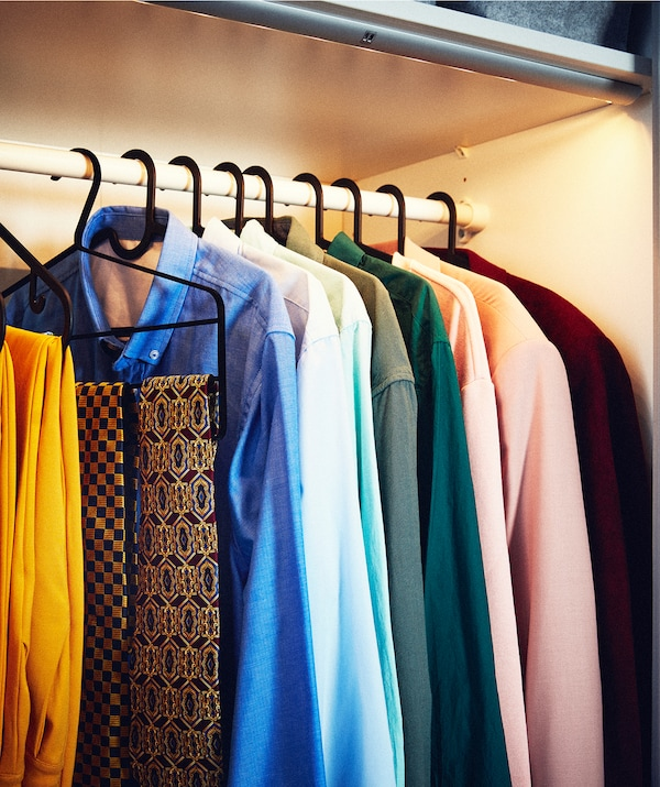 Row of shirts and accessories on hangers on a wardrobe rod, the compartment lit up and fitted with a strip of LED lighting.