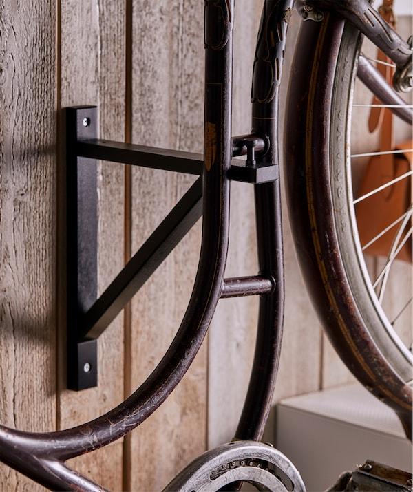 Rower na szafkach EKET jest przymocowany do ściany wspornikiem EKET z pionową gałką MÖLLARP.