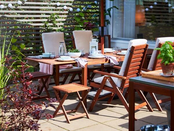 Rozkladací jedálenský stôl, 4 sklápacie kreslá a 2 skladacie stoličky z akácie. Na stole je biely stolovací riad.