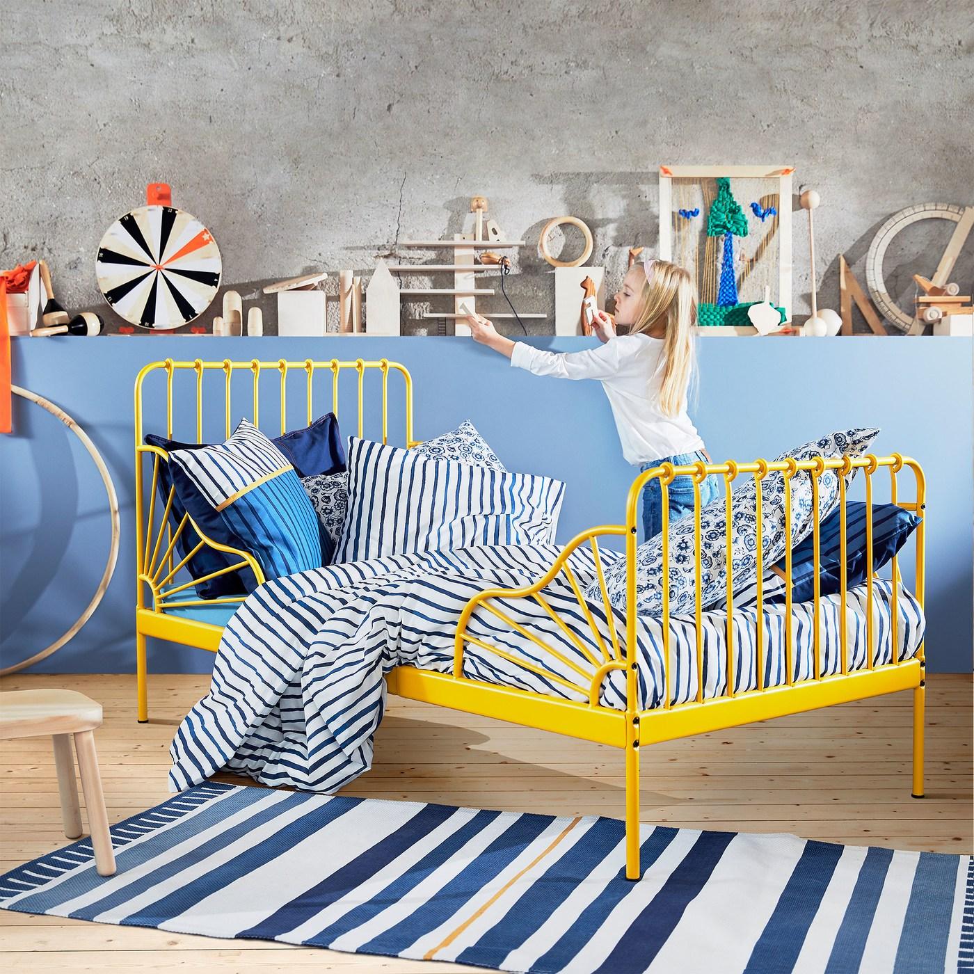 Rozkládací postel MINNEN, kterou lze roztáhnout až na 207 cm. Je práškově nalakovaná na tmavě žlutou barvu a opatřená detaily, které připomínají sluneční paprsky.