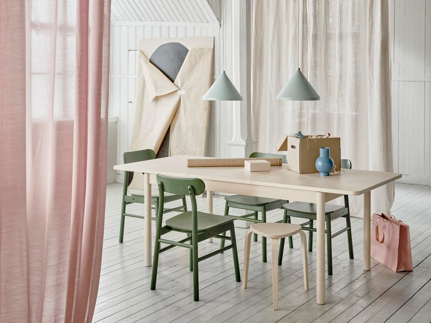 Rozkládací stůl RÖNNINGE v jídelně, na stole je krabice a balicí papíry,nad stolem závěsné lampy