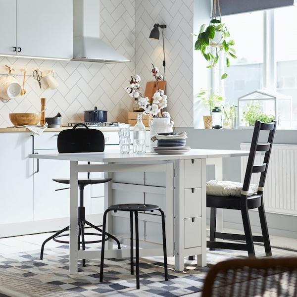 Rozkładan stół NORDEN z krzesłami i stołkami stojący w białej kuchni.