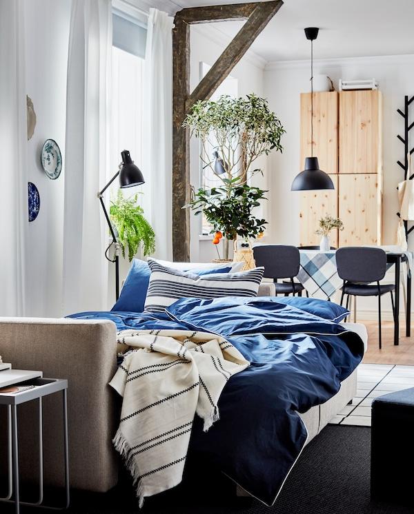 Rozłożona beżowa sofa, ciemnoniebiesko-biała pościel, pled w paski, czarne lampy i szary dywan.