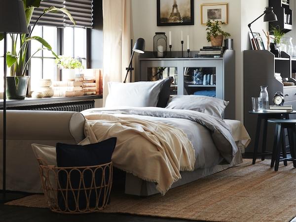 Rozłożona i zaścielona szarą pościelą jasnobeżowa sofa. Za sofą stoi szara witryna z przeszklonymi drzwiami, a na podłodze leży jutowy dywan.