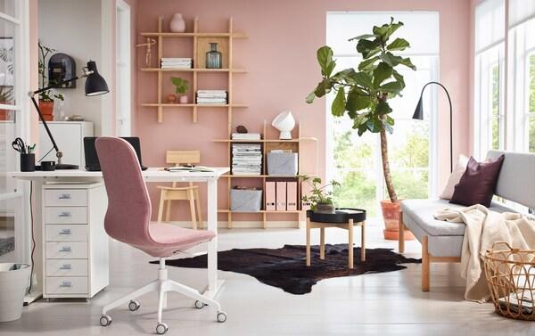 Różowe i białe domowe biuro z biurkiem SKARSTA do pracy na siedząco lub stojąco.