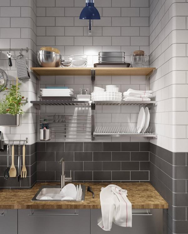 Rozsdamentes acél konyha, fa munkalap, kék lámpa és edényszárító, falra szerelt sínek és polcok.