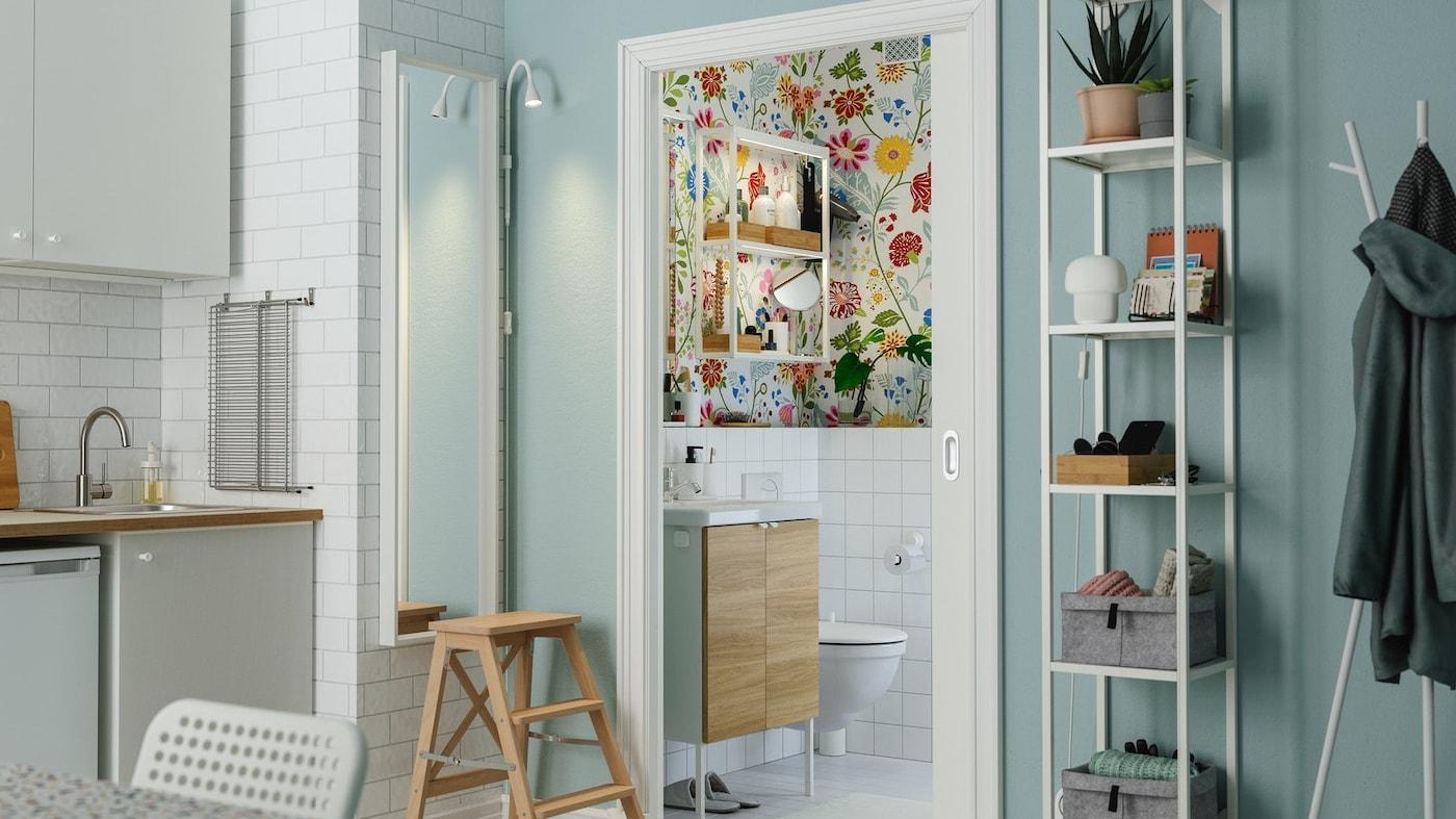 Rozsunięte przesuwane drzwi prowadzące z kuchni do kolorowej łazienki z kwiecistą tapetą i małą szafką z umywalką.