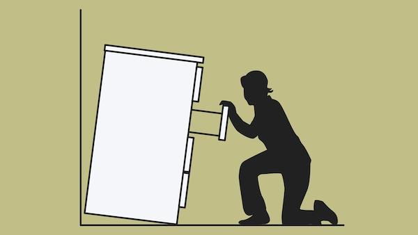 رسم تخطيطي لخزانة ذات أدراج، غير مثبتة على الحائط، تنقلب على امرأة جالسة على ركبتيها وتسحب درجًا.