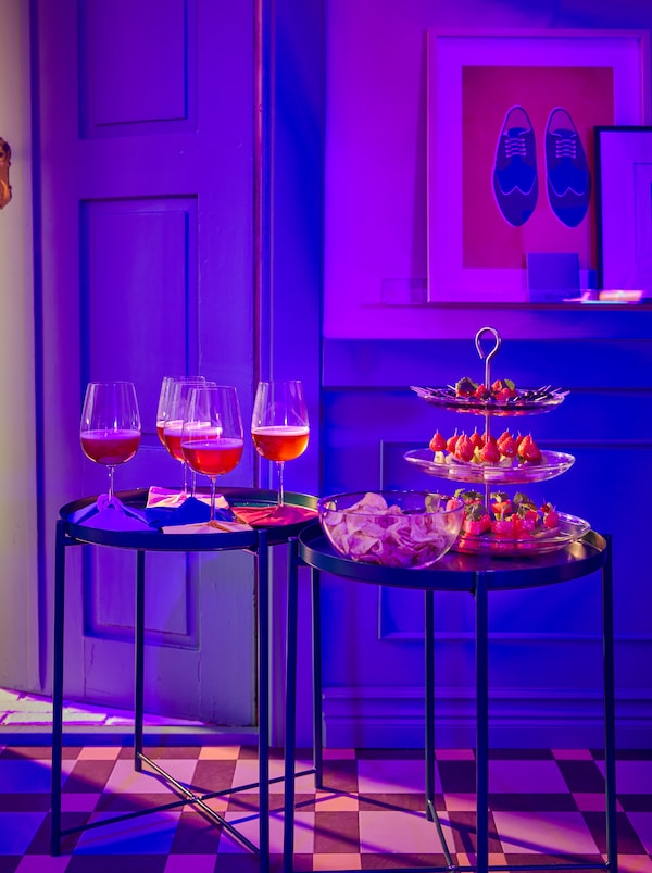 Ruang depan berlantai jubin yang disinari cahaya berwarna ungu dengan juadah alu-aluan dalam bekas hidangan KVITTERA dan minuman dalam gelas wain STORSINT.