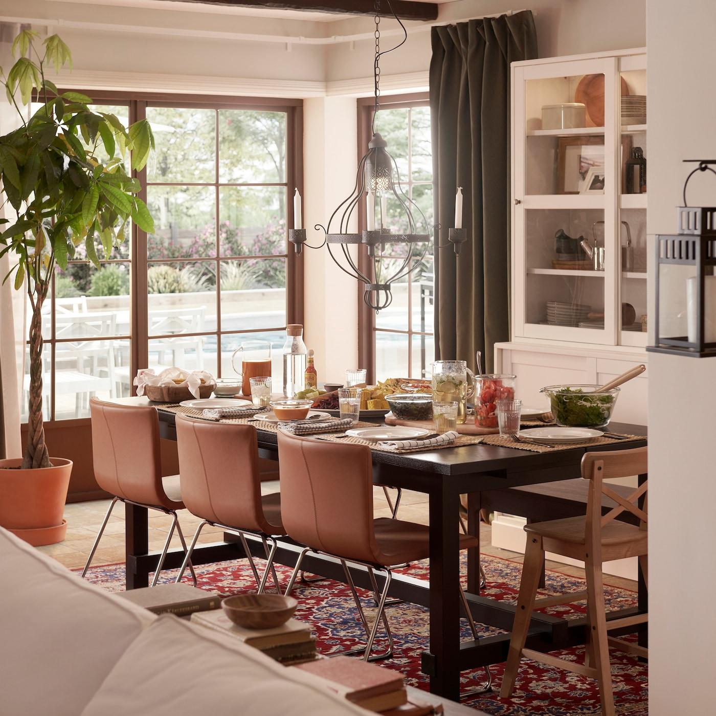 Ruang makan dengan kerusi kulit berwarna coklat keemasan, meja boleh dipanjangkan berwarna hitam, candelier berwarna hitam dan kabinet berpintu kaca berwarna putih.