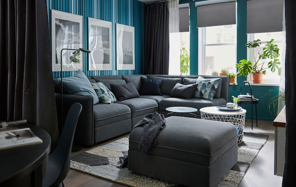 Ruang tamu berangin dengan tingkap besar; sofa penjuru, dinding dan langsir dalam warna pekat; beberapa meja kopi kecil, tumbuh-tumbuhan.