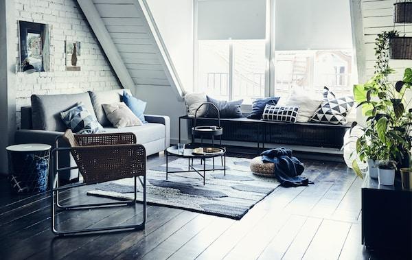 Ruang tamu hitam putih dengan bumbung cerun, sofa berwarna kelabu, kerusi berlengan rotan dan ambal berstruktur besar.