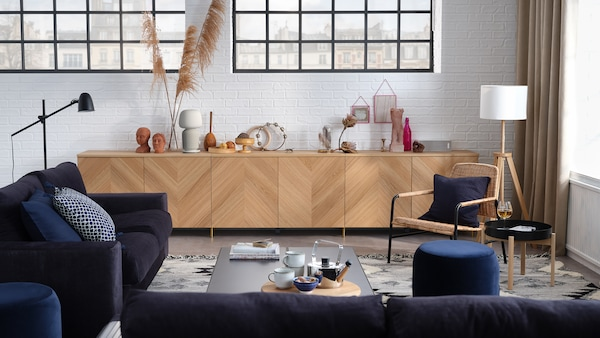 Ruang tamu yang bergaya dengan sofa 3 tempat duduk, katil sofa 2 tempat duduk, kombinasi storan dengan pintu dan kerusi berlengan.