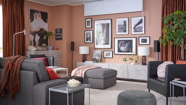 Ruang tamu yang mempunyai dinding yang penuh dengan kerja seni berbingkai, bidai bergulung penghalang cahaya, langsir penggelap ruang dan sofa 3 tempat duduk.