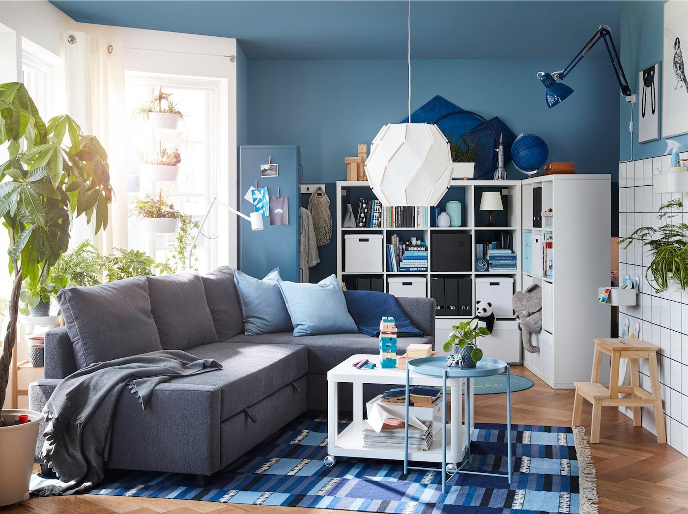Ruang tamu yang mempunyai katil sofa penjuru berwarna kelabu gelap, ambal bercorak berwarna biru dan unit rak bebas dengan ruang di belakangnya.