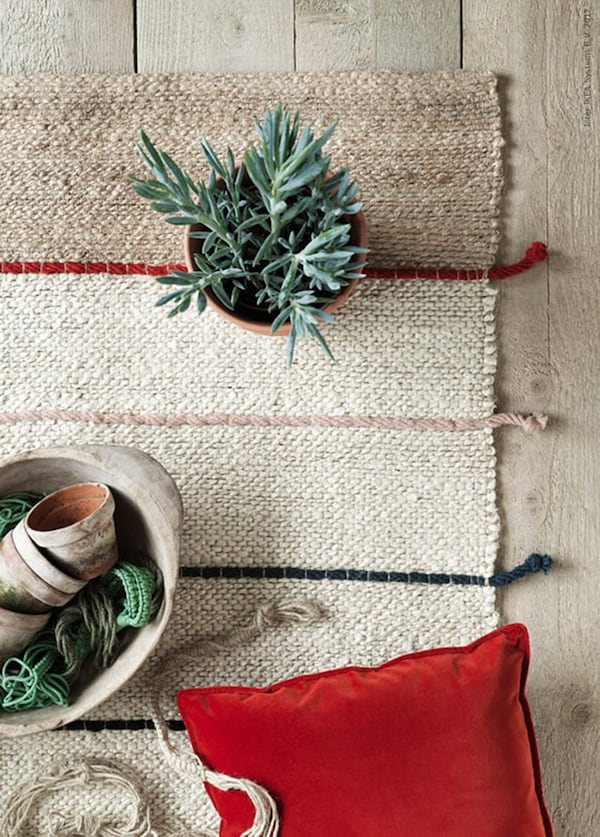 Rug with a red cushion, a plant and light, wooden accessories