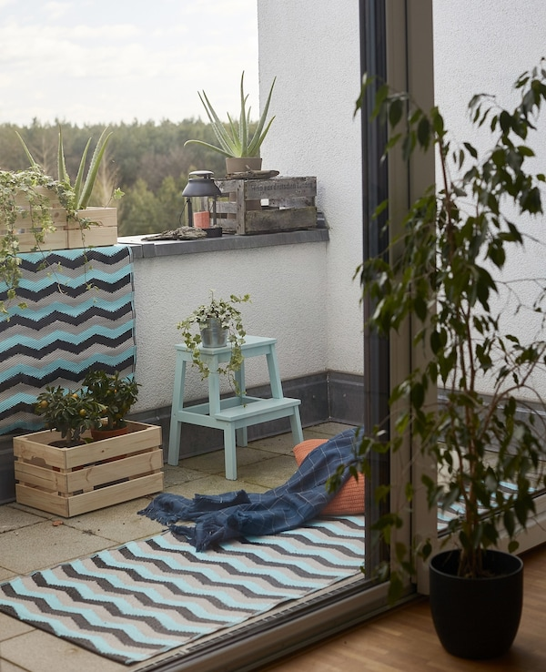 Rugs, throws, plants and crates on a balcony.
