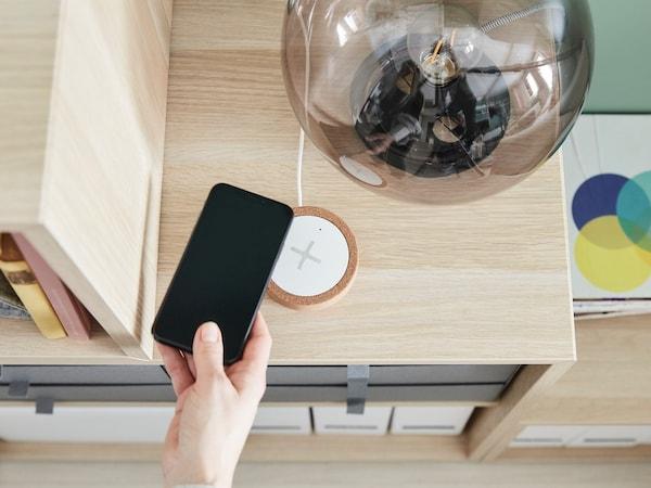Ruka držící chytrý telefon nad bezdrátovou nabíječkou NORDMÄRKE.