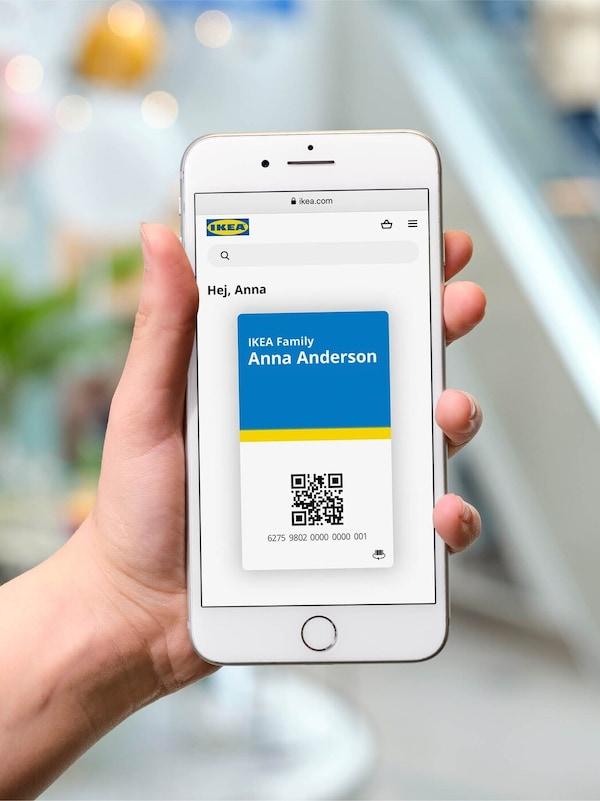 Ruka držící mobilní telefon s digitální kartou IKEA na displeji