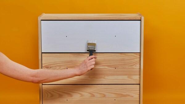 Ruka natiera zásuvku bielou farbou.