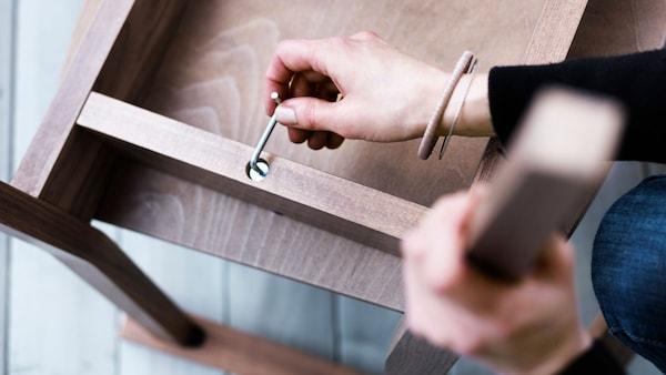 Ruka osoby provádějící montáž nábytku pomocí imbusového klíče