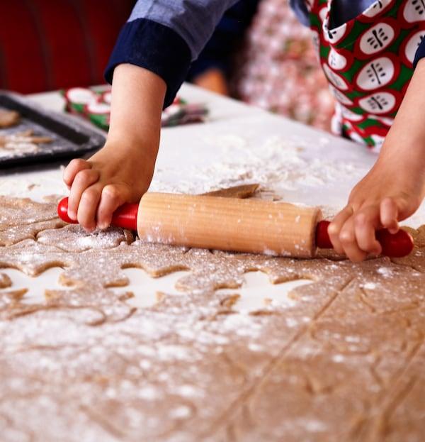 Ruke djeteta s pregačom koje drži valjak i širi tijesto za keksiće s đumbirom prekriveno brašnom izrezano s pomoću kalupa.
