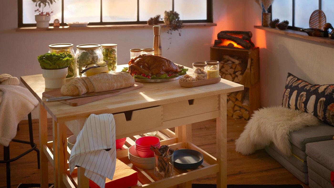 Rum indrettet som en hyggelig bjælkehytte med en lille, festlig buffet anrettet på 2 rulleborde og et kunstigt ildsted i hjørnet.